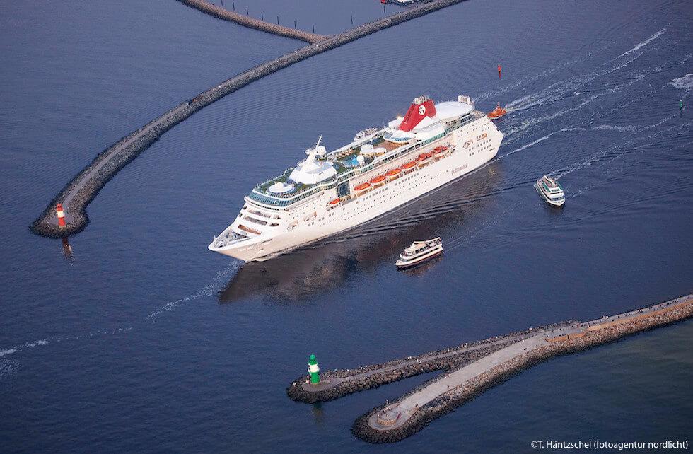 Ein Kreuzfahrtschiff verlässt den Hafen Rostock und befindet sich dabei zwischen West- und Ostmole des Ostseebades Rostock-Warnemünde. Aus der Vogelperspektive sieht man lediglich das Kreuzfahrtschiff in Begleitung von zwei kleinen Ausflugsdampfern und Teile der Mole