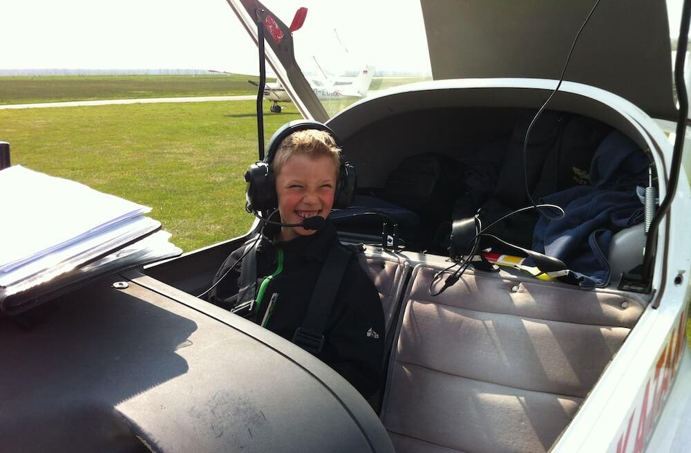 ca. 10 Jahre alter Junge sitzt in einem zweisitzigen Flugzeug auf dem Flugplatz im brandenburgischen Oehna und ist sichtlich erfreut nach seinem ersten Flug.
