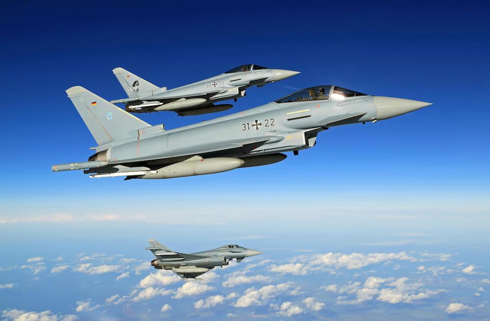 3 Militärflugzeuge von Typ Eurofighter von der Seite mit kräftig blauem Himmel als Hintergrund und ein paar weißen Wolken